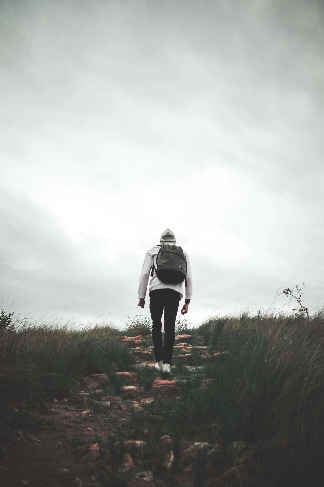 A person with a backpack and a hood is walking up a stony path.