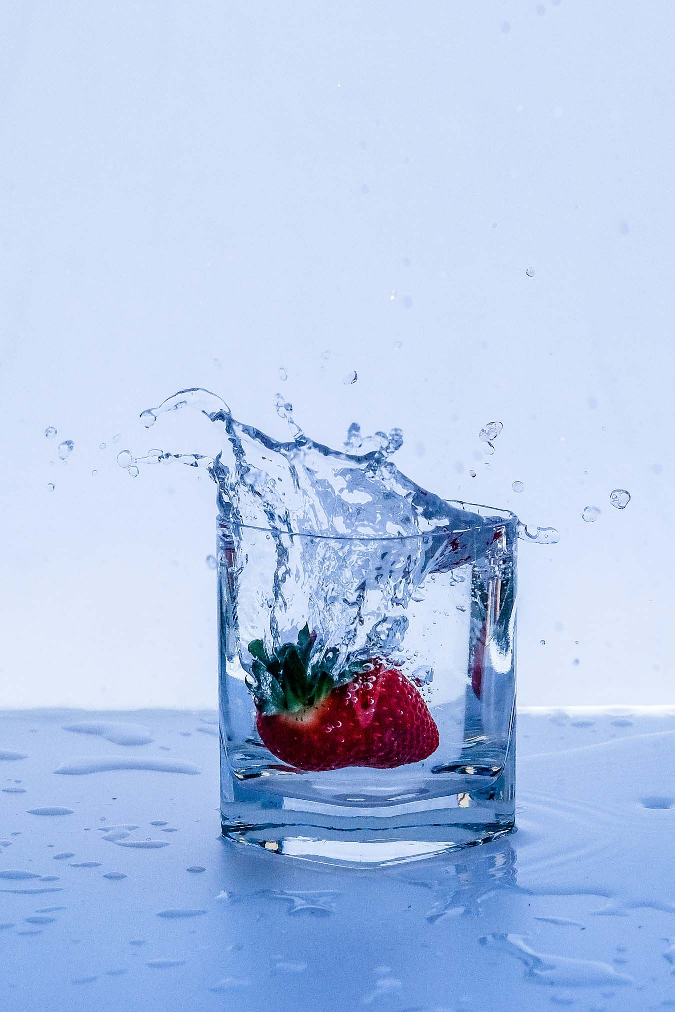 A red strawberry falls into a full glass of water. Water splashes out.
