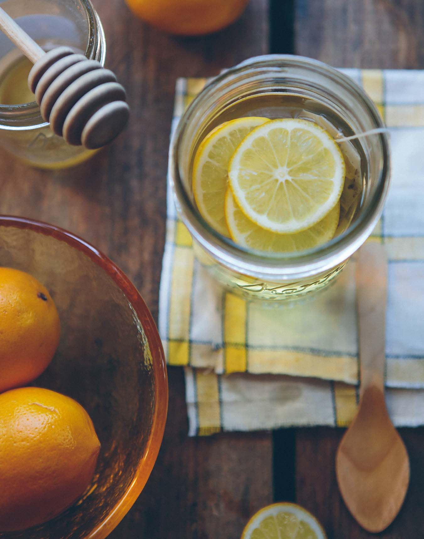 Lemon tea in a glass mug stands on a cloth - honey jar and orange citrus fruits next to it