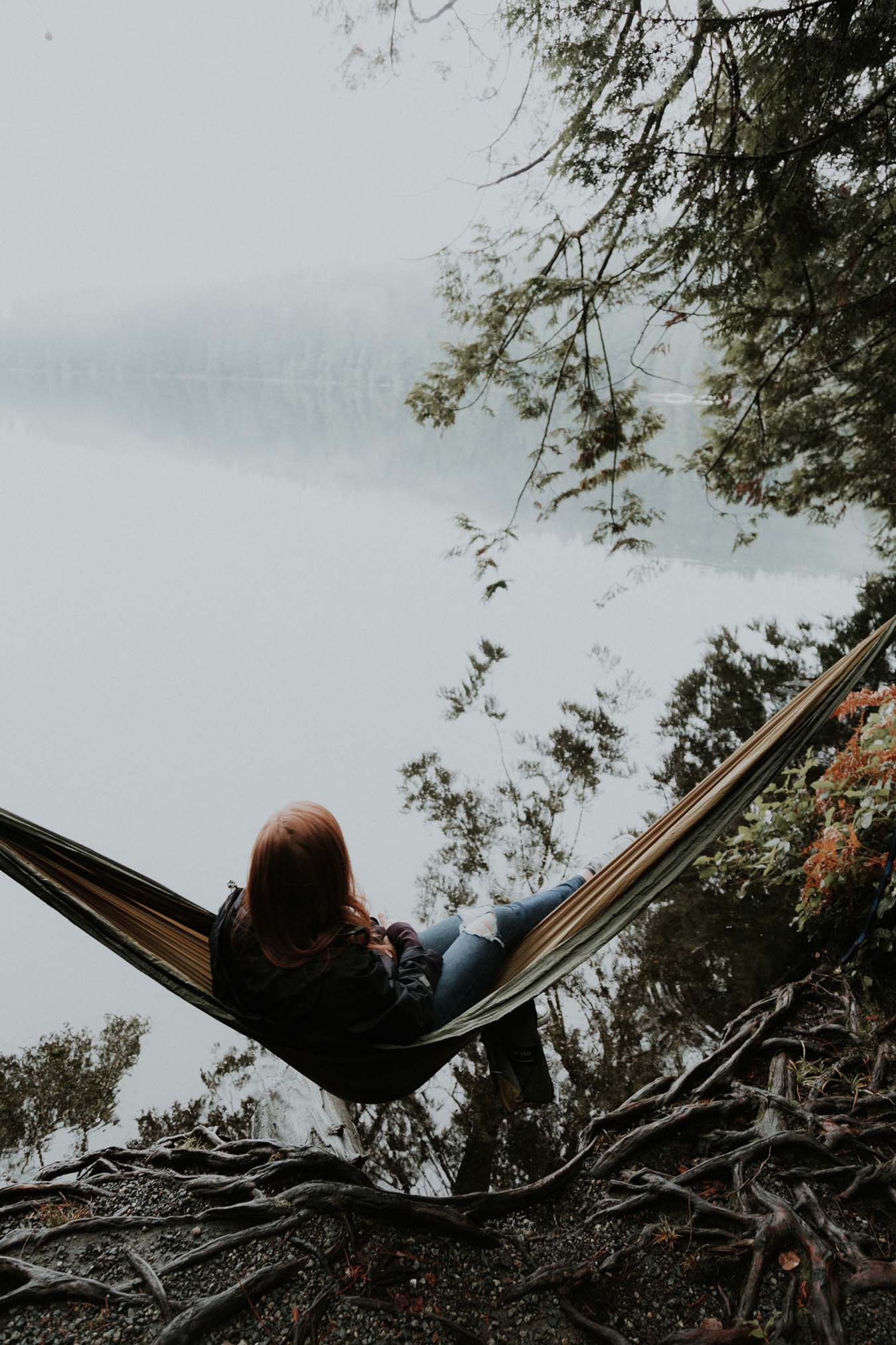 Young red-haired girl dangles her soul in a hammock by the lake
