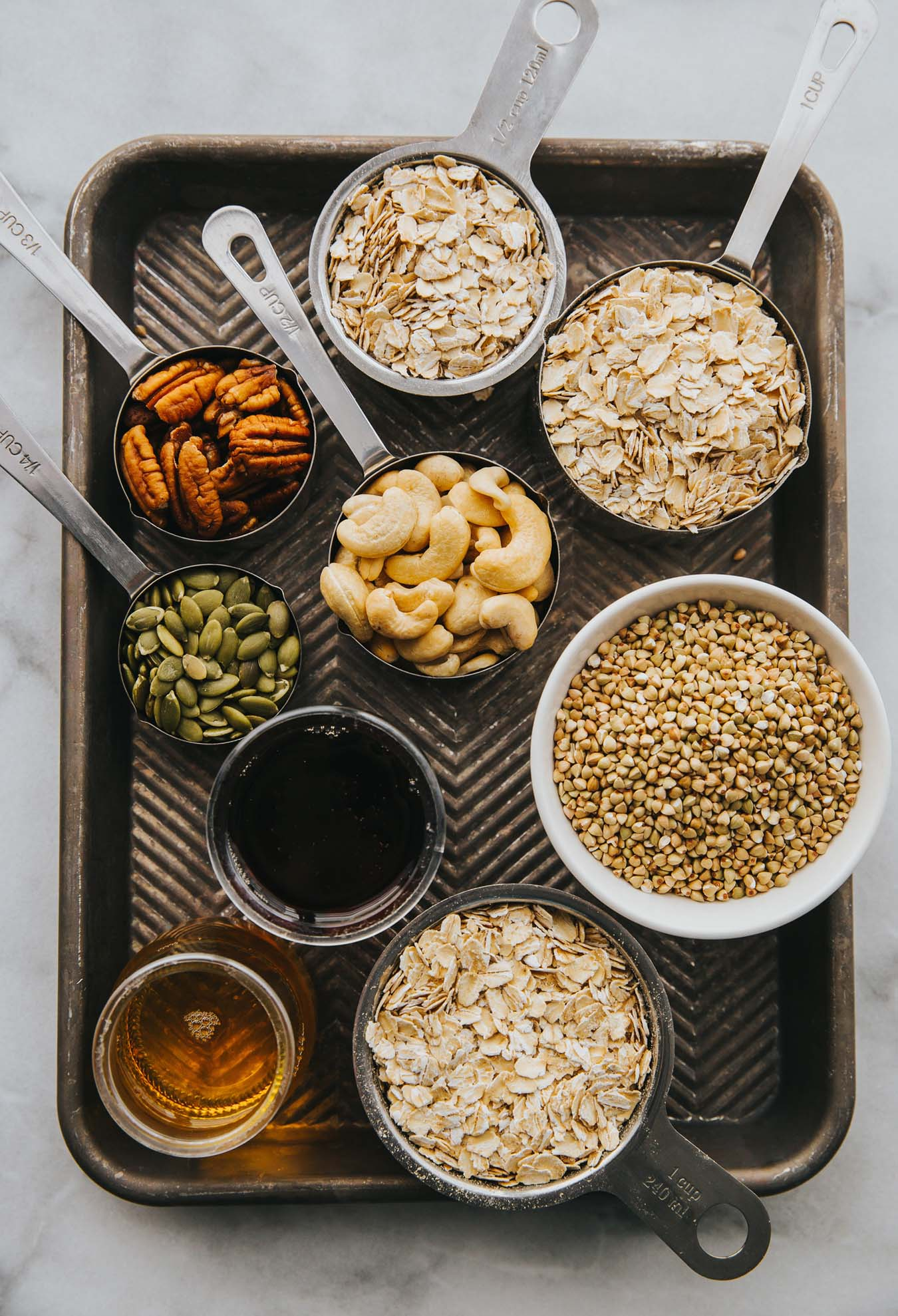 On an old baking sheet are small bowls with various ingredients such as cashews, buckwheat, oatmeal, pecans and pumpkin seeds.