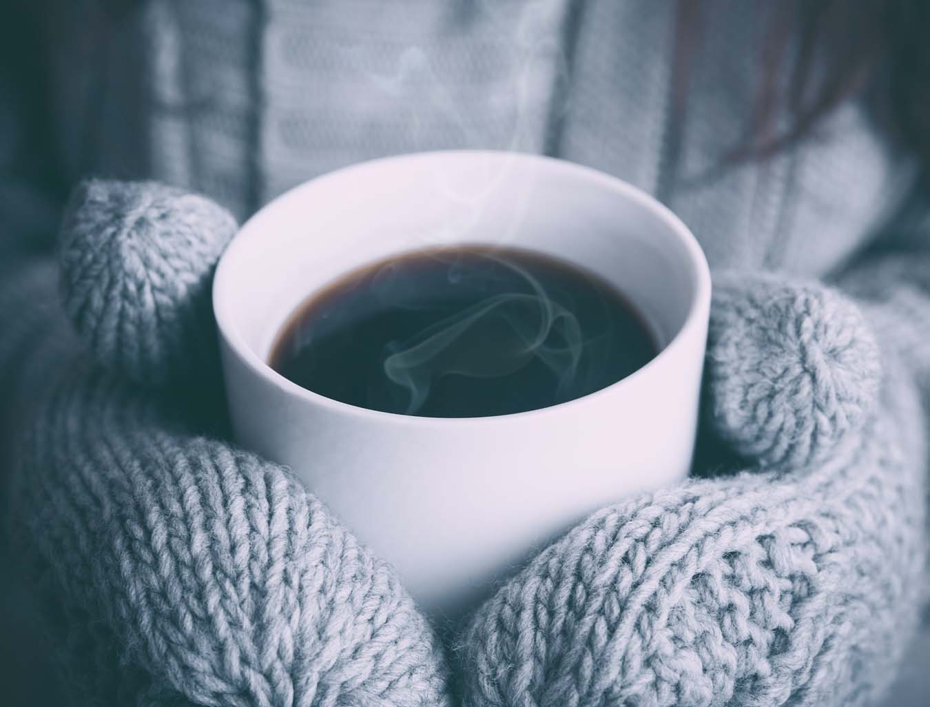 Hands in thick woolen gloves hold a cup of hot tea.