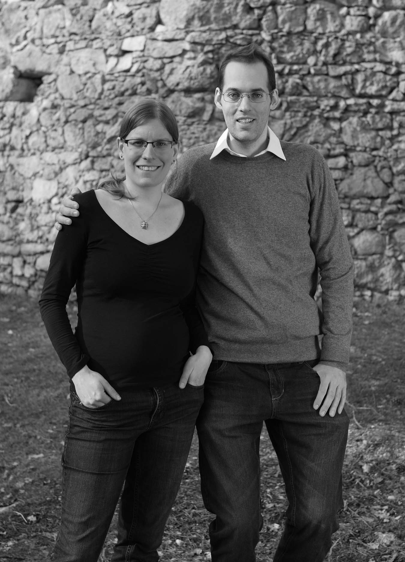 Ann-Katrin and Thomas in elegant outfit outside - stone wall as background