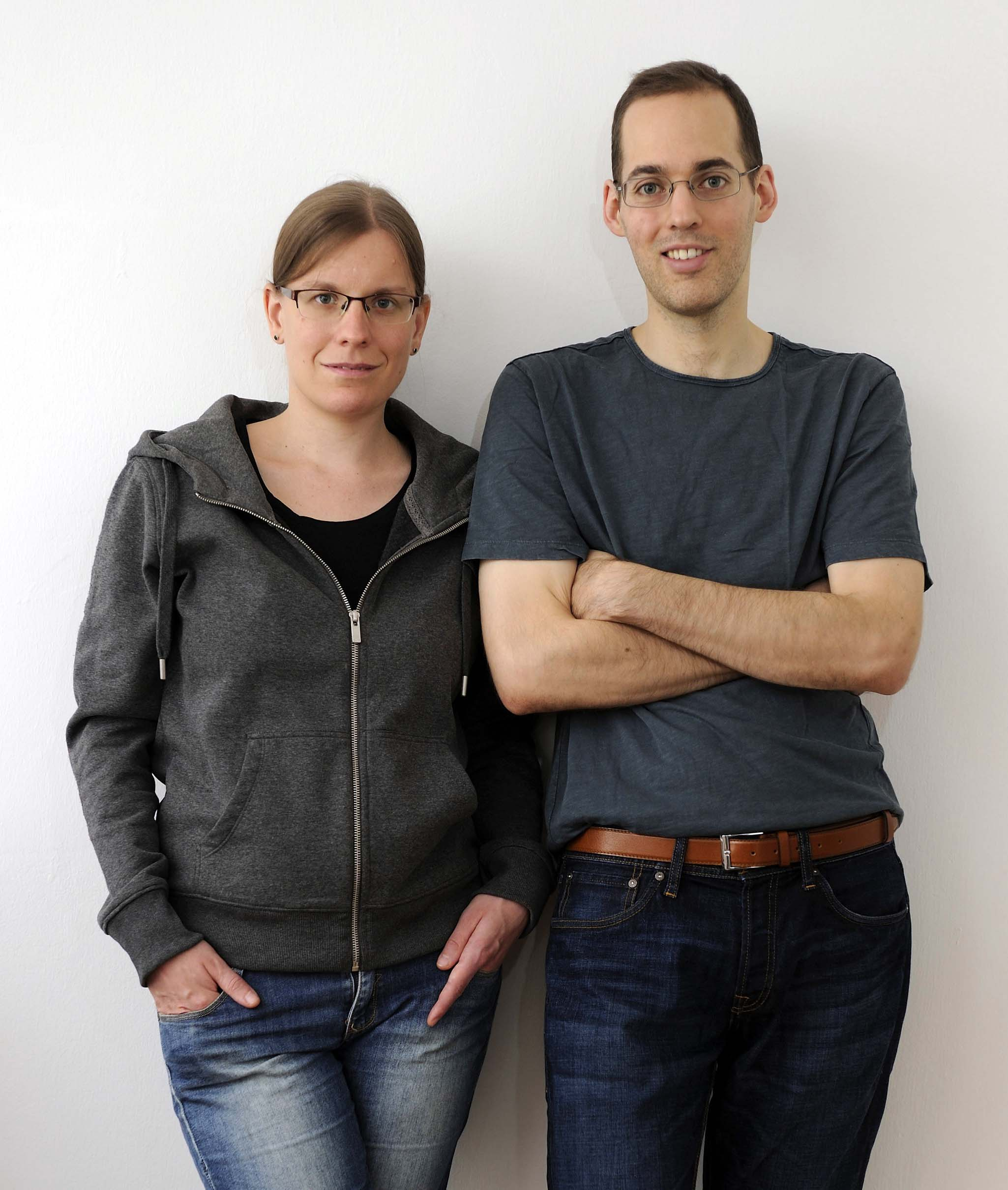 Thomas and Ann-Katrin in casual outfit standing in front of white wall